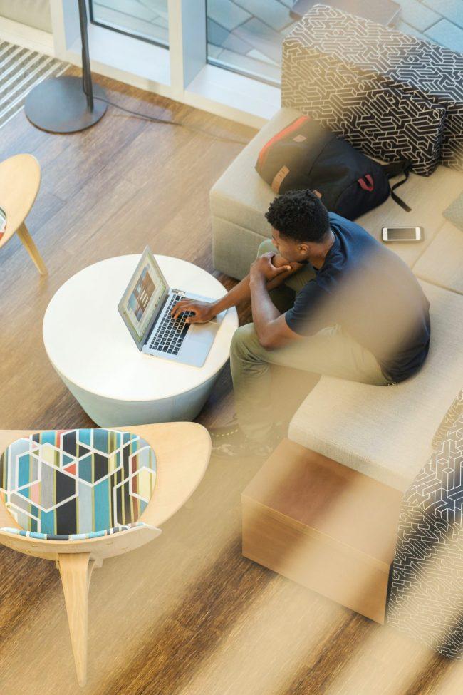 Man Using Gray Laptop While Sitting On Beige Sofa 1251862
